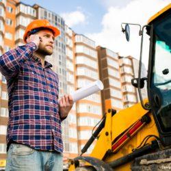 Engenheiro falando ao telefone na frente de uma obra de construção civil.